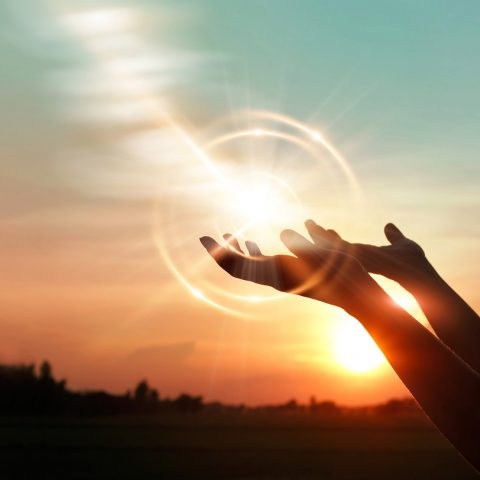 Mains tendues en prière et halo de lumière, Oasis