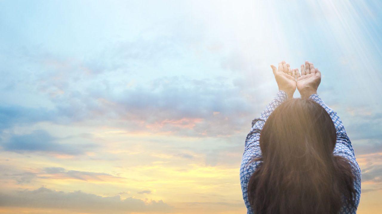 Femme tendant les mains vers le ciel, Oasis